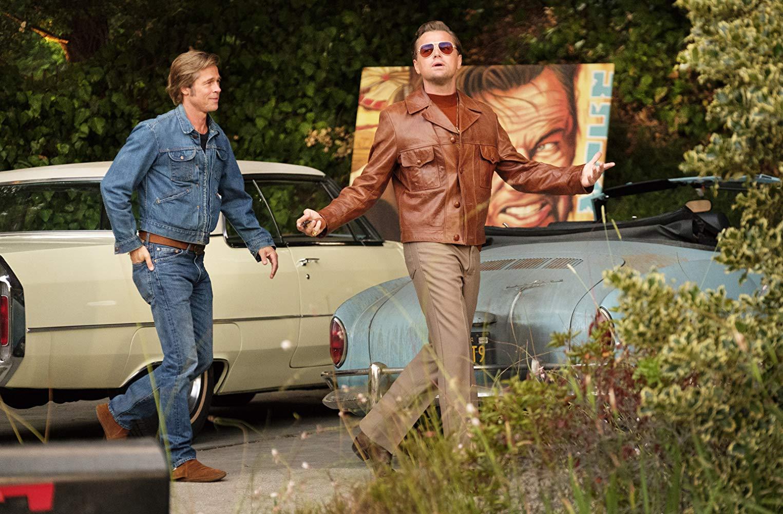 Brad Pitt και Leonardo DiCaprio περπατούν μπροστά από αυτοκίνητα αντίκα