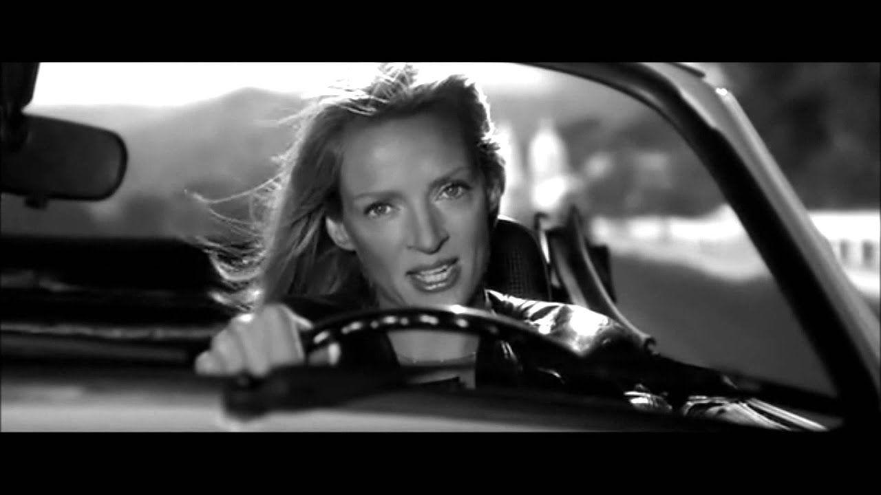 Ασπρόμαυρη φωτογραφία της Ούμα Θέρμαν να οδηγάει