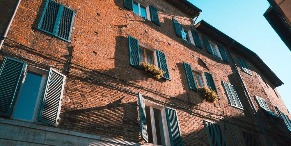 Παλιό κτίριο φτιαγμένο με τούβλα και παράθυρα με πρασινάδα