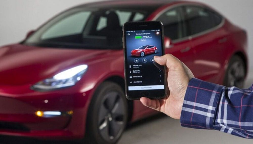 Φωτογραφία που δείχνει άνθρωπο που φωτογραφίζει ένα κόκκινο Tesla