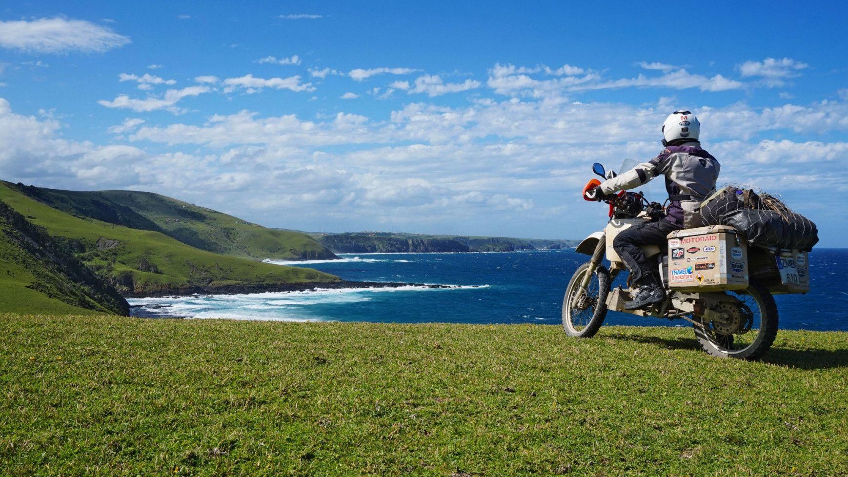 αναβάτης σε μοτοσυκλέτα θαυμάζει τη θέα στη θάλασσα