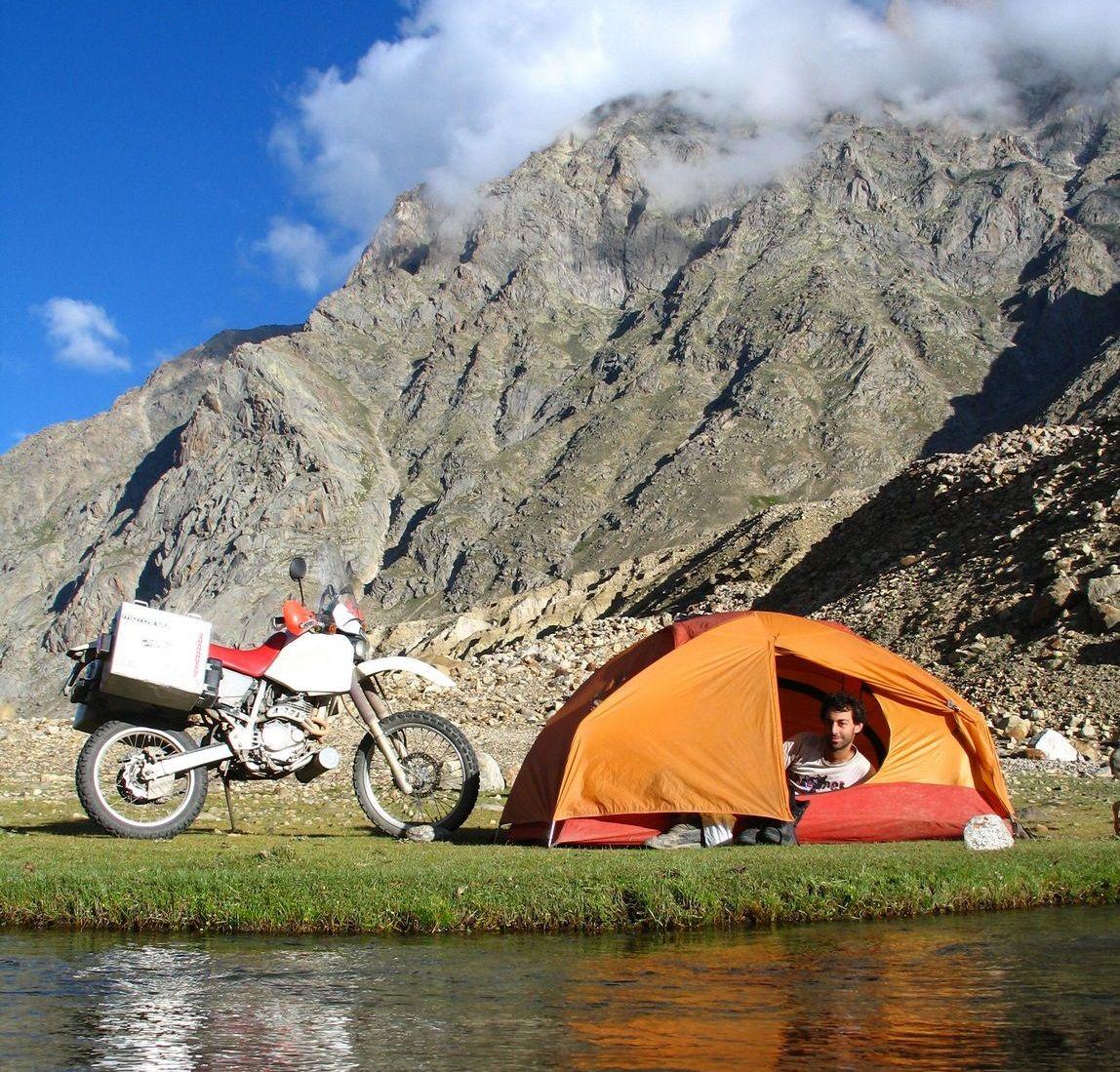 Μοτοσυκλέτα σίπλα σε πορτοκαλί σκηνή στους πρόποδες βουνού