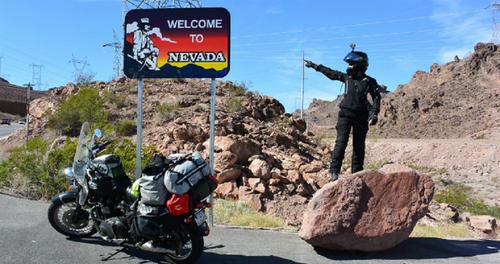 παρκαρισμένη μοτοσυκλέτα μπροστά από πιμακίδα στη Νεβάδα και άνθρωπο πάνω σε βράχο