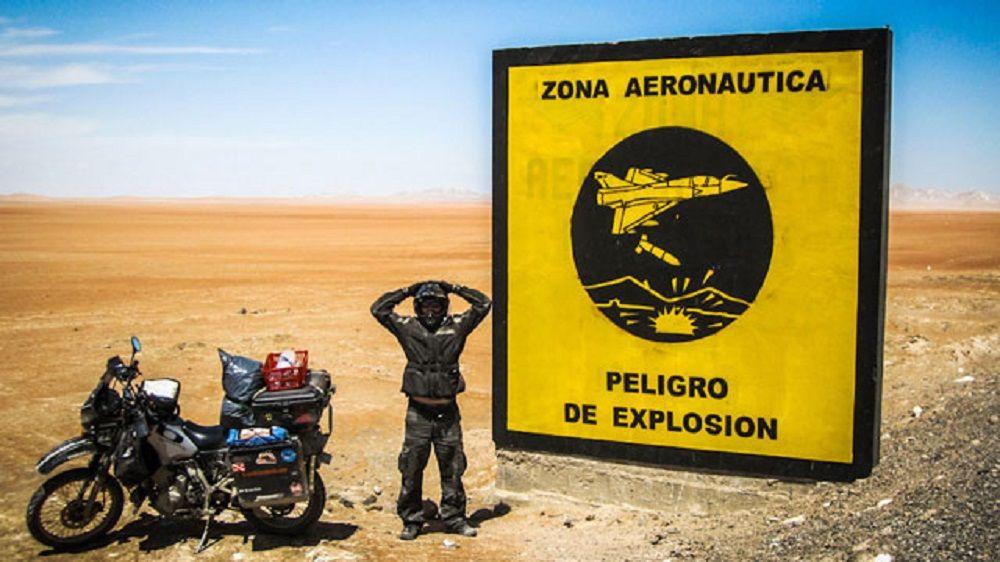 Μοτοσυκλετιστής μπροστά από κίτρινη ταμπέλα σε ερημική τοποθεσία