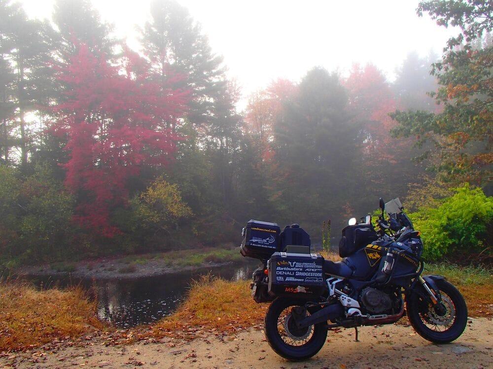 Μοτοσυκλέτα παρκαρισμένη σε πολύχρωμο δάσος