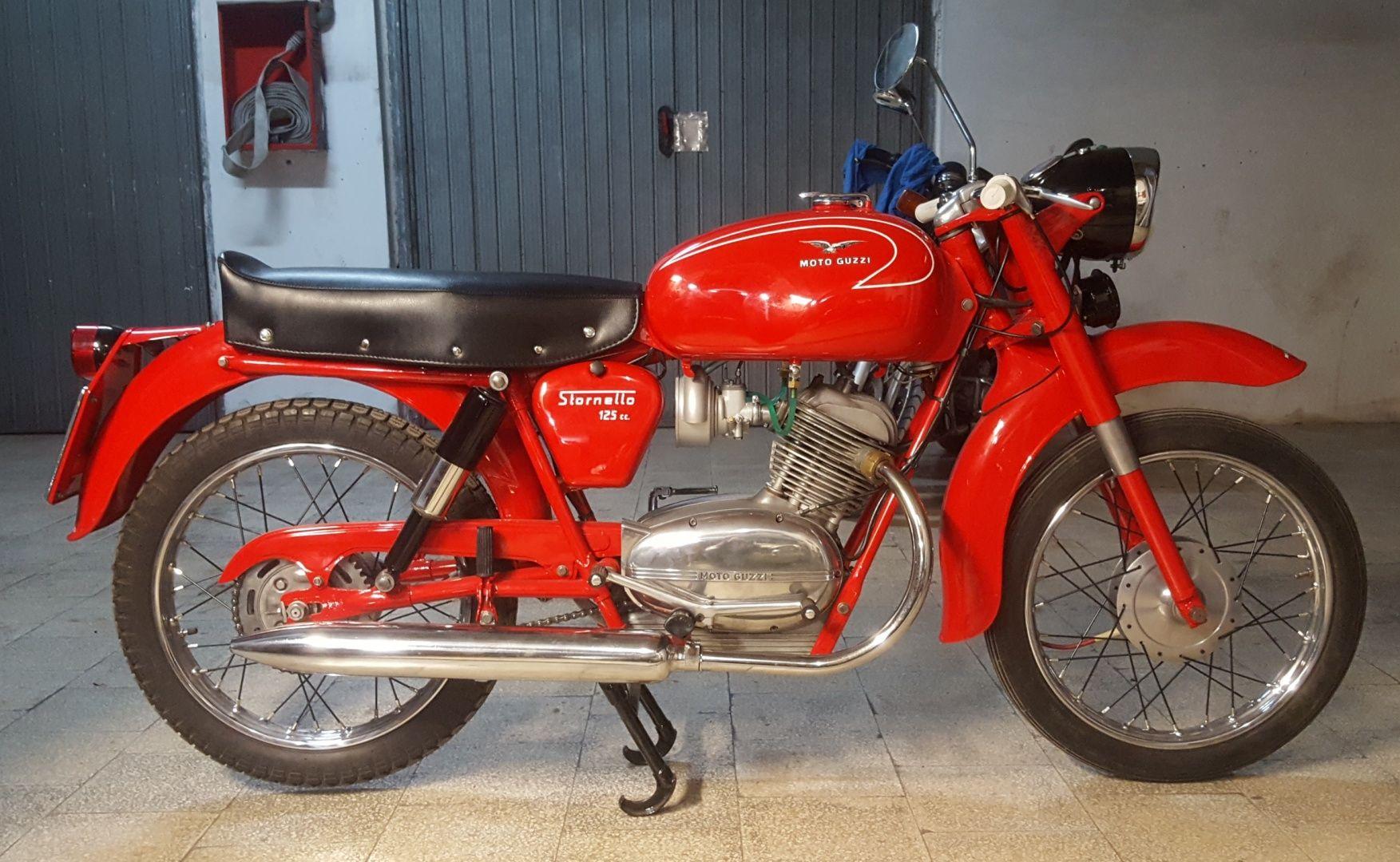 Κόκκινη Moto Guzzi Stornello παρκαρισμένη μπροστά από γκρι πόρτα