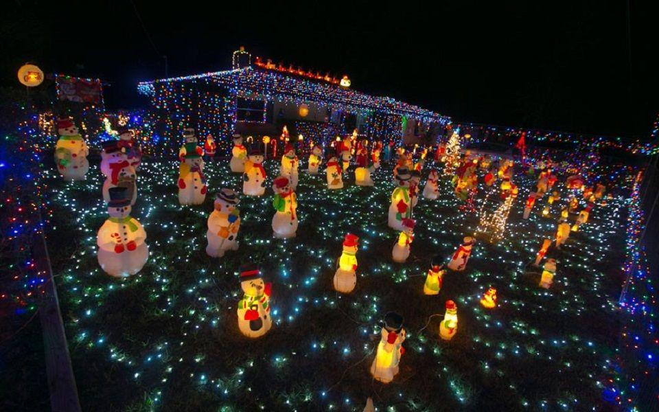 Χριστουγεννιάτικοι χιονάνθρωποι λάμπες σε αυλή σπιτιού με πολύχρωμα λαμπάκια