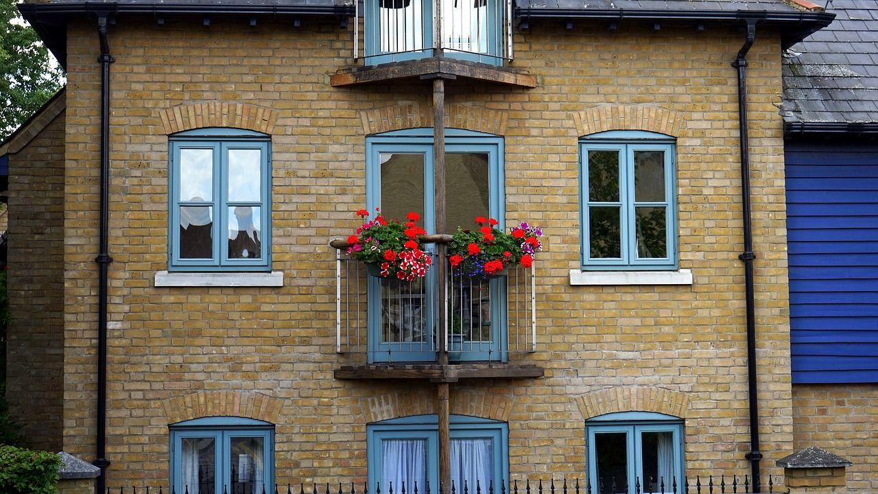 Πρόσοψη σπιτιού με γαλάζια παράθυρα και μπαλκόνι με κόκκινα λουλούδια