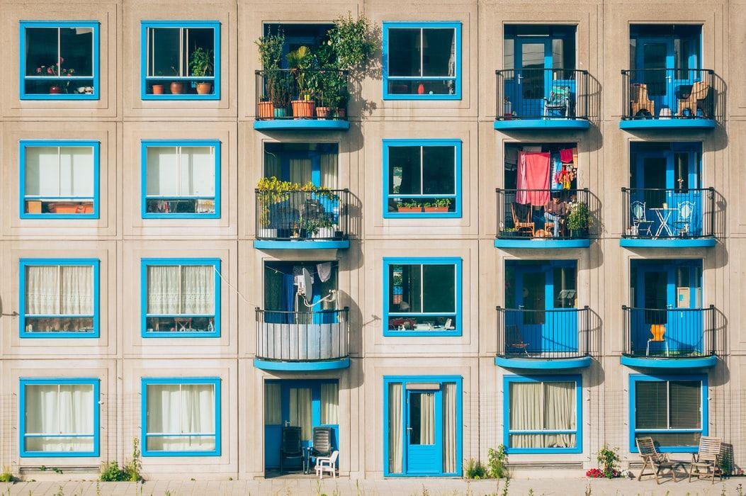Πολυκατοικία με γαλάζια μπαλκόνια και παντζούρια