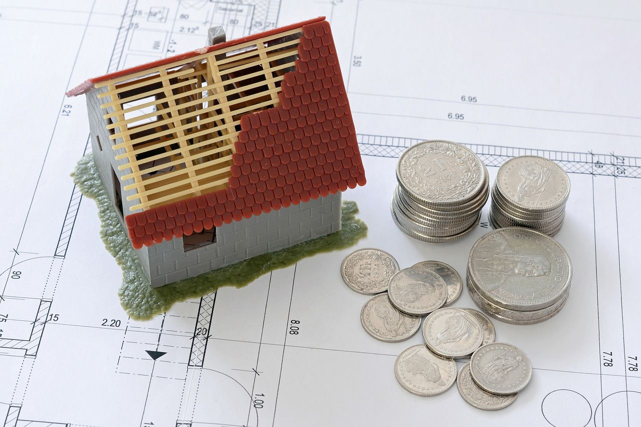 μινιατούρα σπιτιού και κέρματα δίπλα, πάνω σε σχέδιο για σπίτι