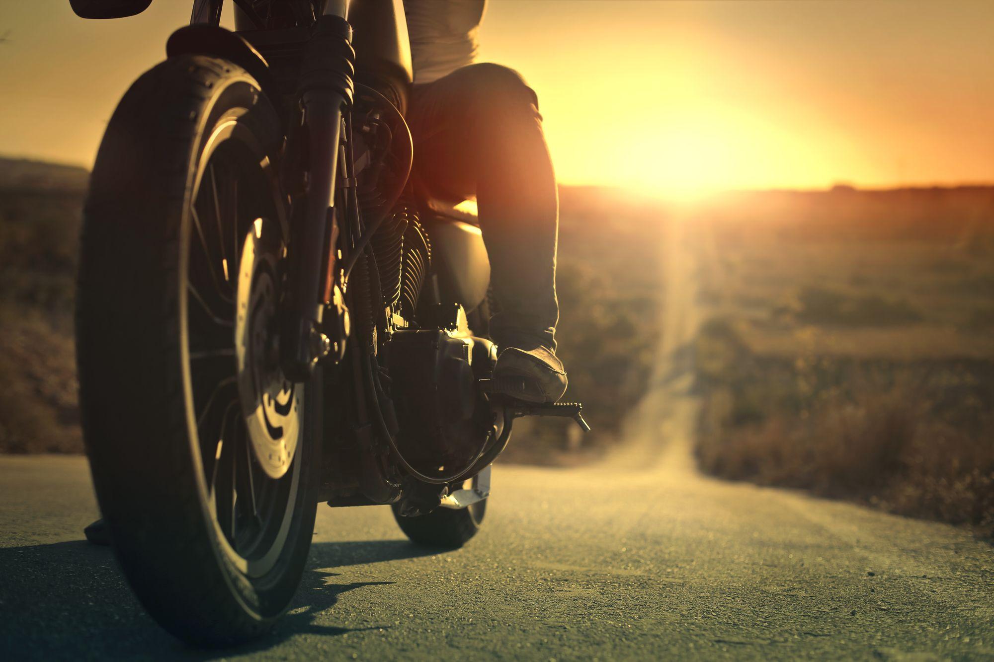 Αναβάτης πάνω σε μηχανή με φόντο το ηλιοβασίλεμα