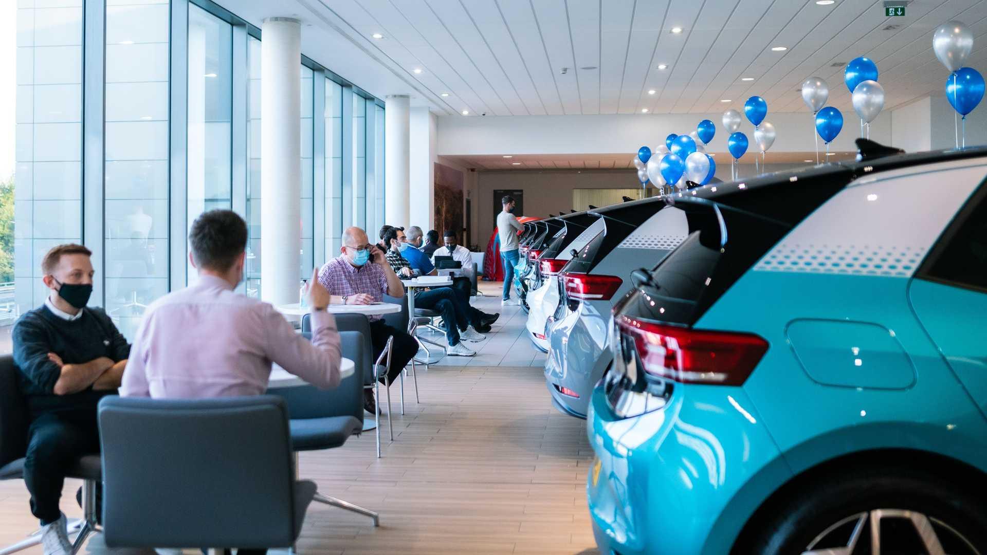 Αυτοκίνητα παρκαρισμένα σε εκθεσιακό χώρο και άνθρωποι πίνουν καφέ