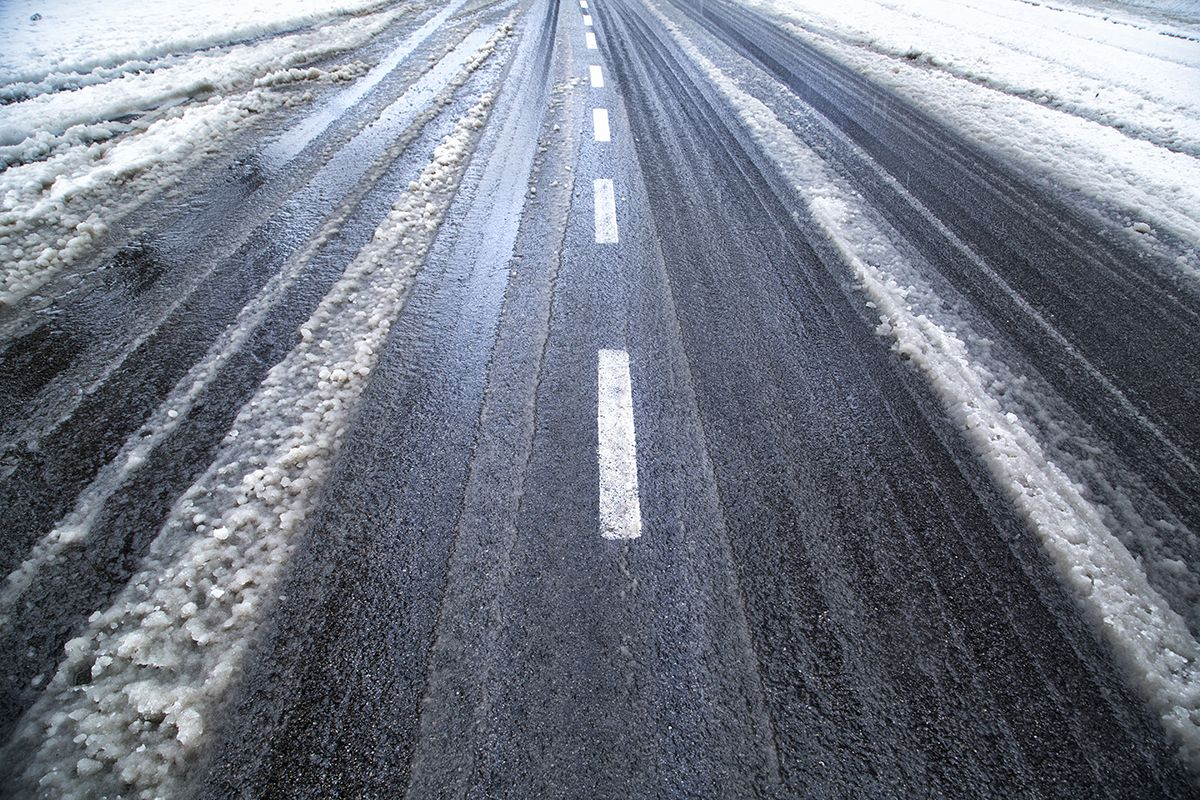 Παγωμένος δρόμος με λιωμένο χιόνι στις άκρες