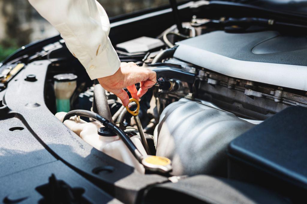 Ένα χέρι ελέχγει την στάθμη των λαδιών του κινητήρα ενός αυτοκινήτου