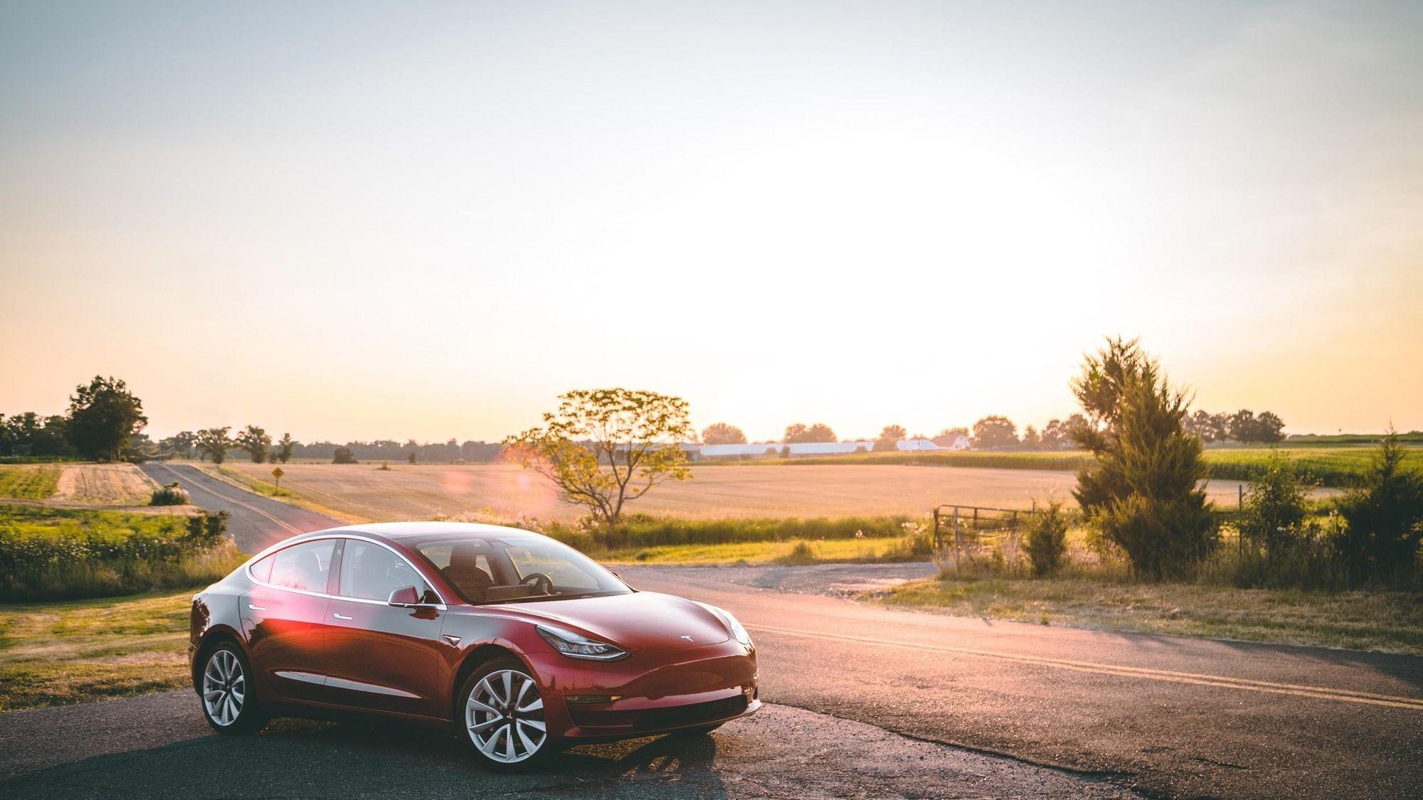 κόκκινο παρκαρισμένο Tesla στην άκρη του δρόμου