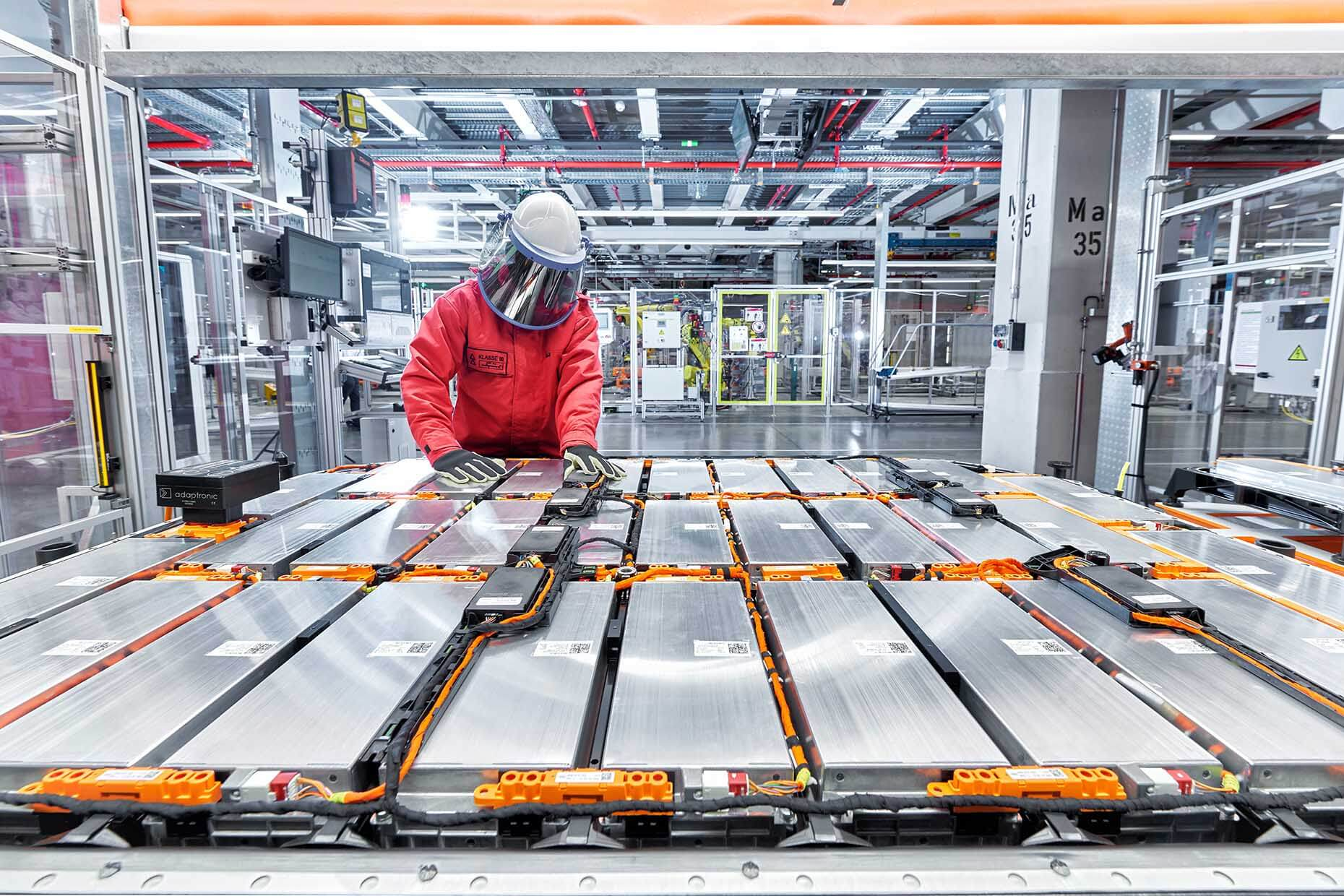 εργάτης επιβλέπει μια σειρά από μπαταρίες για ηλεκτρικά αυτοκίνητα