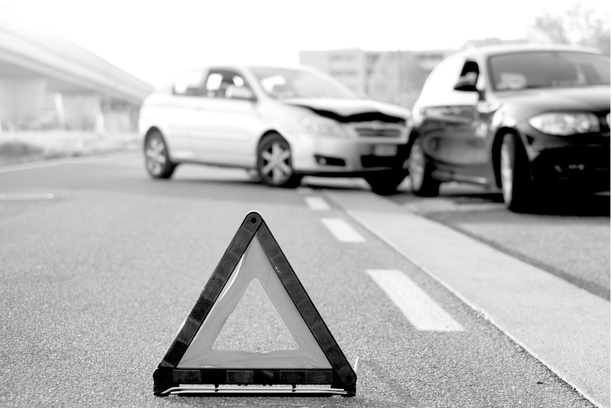 τρίγωνο προειδοποίησης στημένο στην άσφαλτο και πίσω οχήματα που έχουν τρακάρει μεταξύ τους