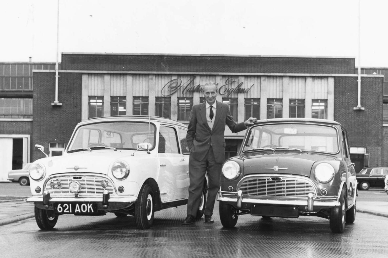 Ο σχεδιαστής Ισιγώνης ποζάρει ανάμεσα σε 2 μοντέλα Morris Mini Minor