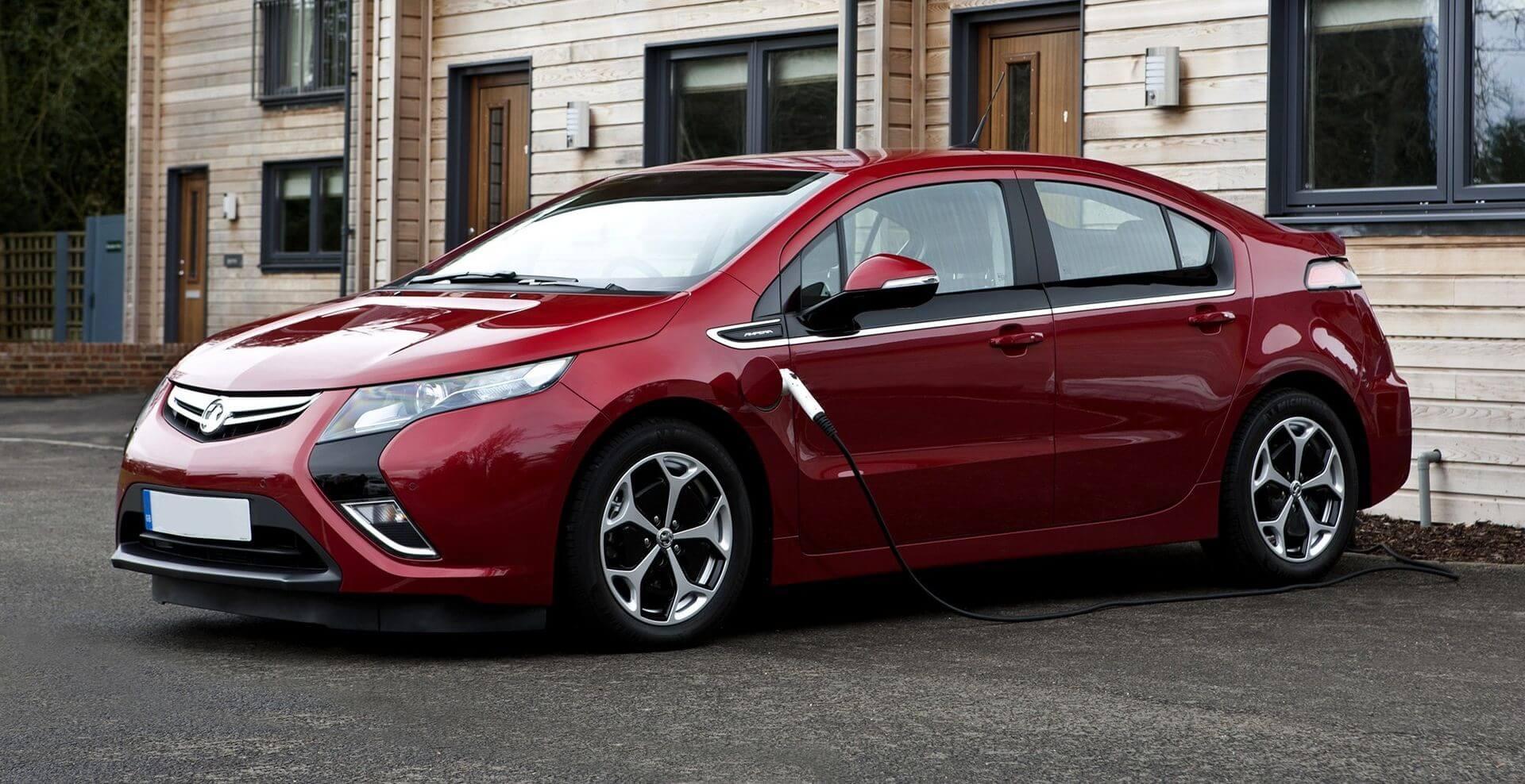 γυαλιστερό κόκκινο αυτοκίνητο παρκαρισμένο έξω από σπίτι φορτίζει σε ιδιωτικό wallbox