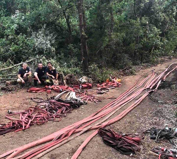 Τρεις πυροσβέστες κάθονται αγκαλιασμένοι μέσα στο δάσος δίπλα σε πυροσβεστικές μάνικες