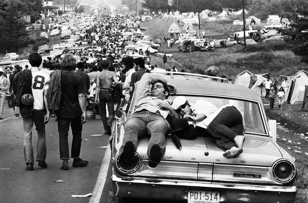 άνθρωποι κοιμούνται πάνω στο καπό του αυτοκινήτου ενώ πλήθος άλλων είναι στο δρόμο