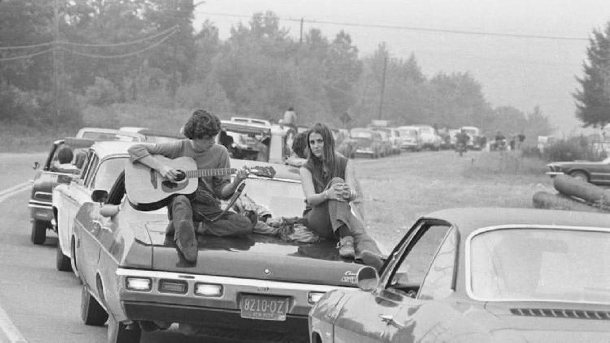 μποτιλιαρισμένα αυτοκίνητα και ένας άνδρας παίζει κιθάρα πάνω στο αυτοκίνητό του για να περάσει η ώρα