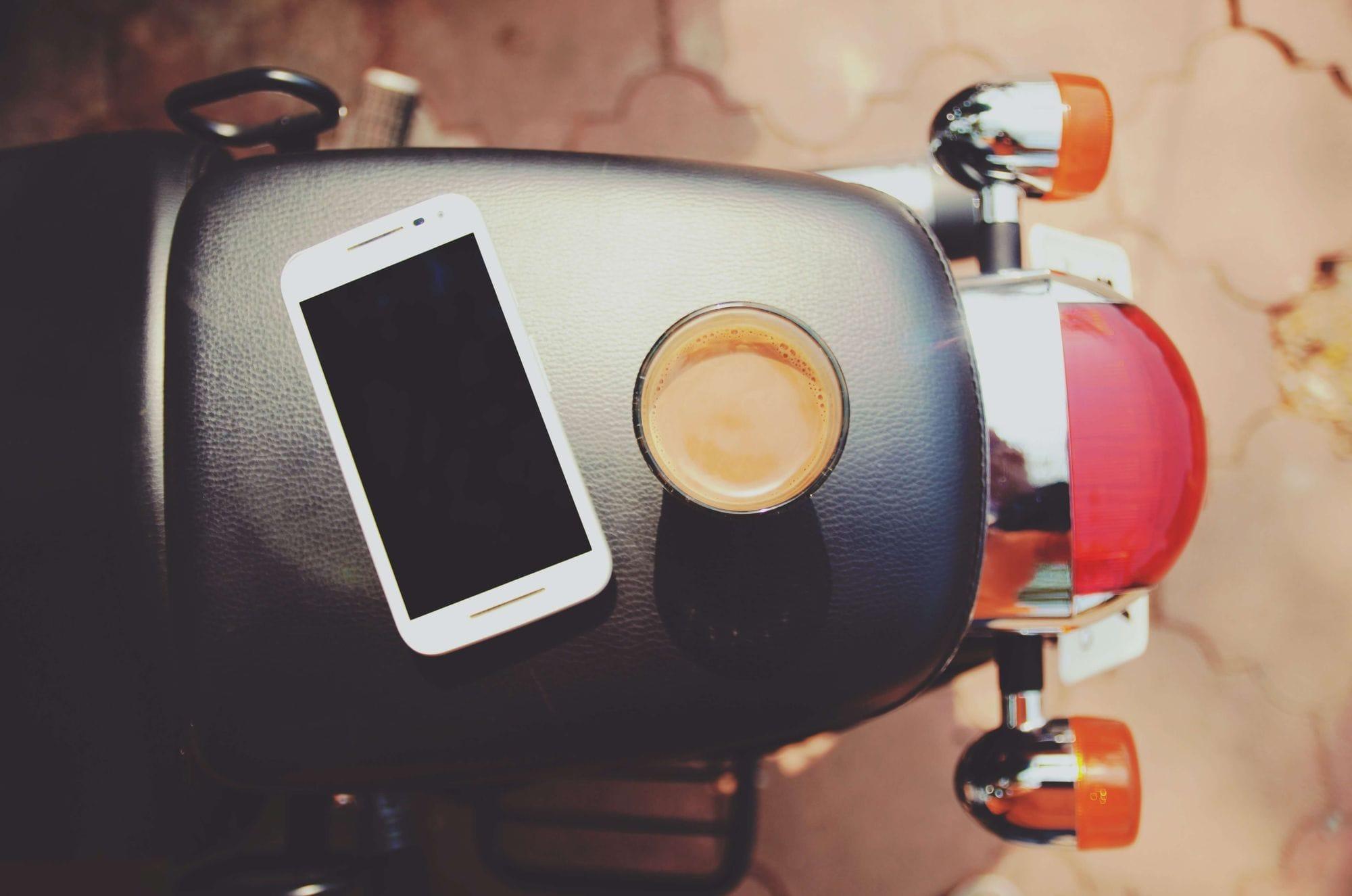Κινητό και καφές ακουμπισμένα σε σέλα μηχανής